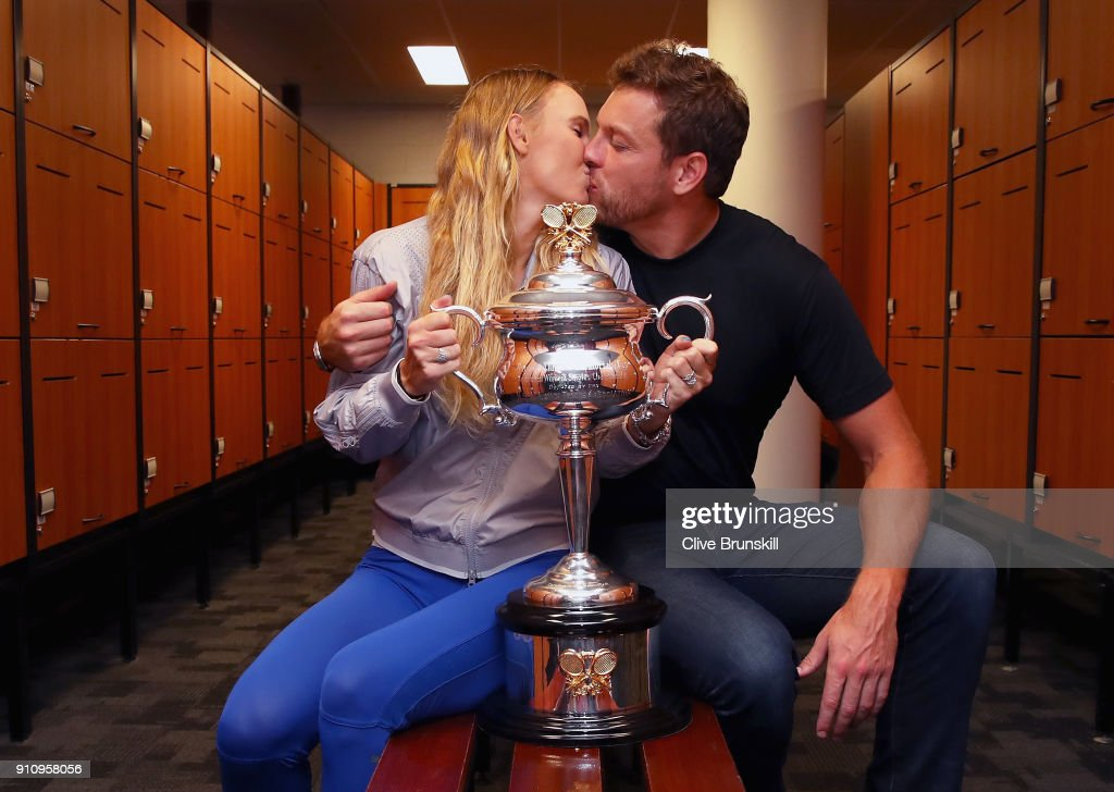 Caroline Wozniacki of Denmark kisses fiance David Lee as they pose with the Daphne Akhurst Trophy in the locker-room after winning the Women's Singles Final against Simona Halep of Romania on day 13 of the 2018 Australian Open at Melbourne Park on January 27, 2018 in Melbourne, Australia.