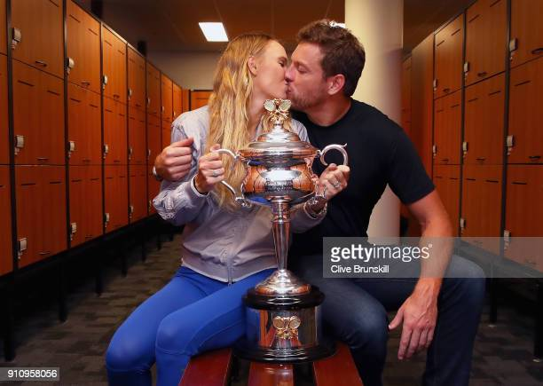 Caroline Wozniacki of Denmark kisses fiance David Lee as they pose with the Daphne Akhurst Trophy in the locker-room after winning the Women's...