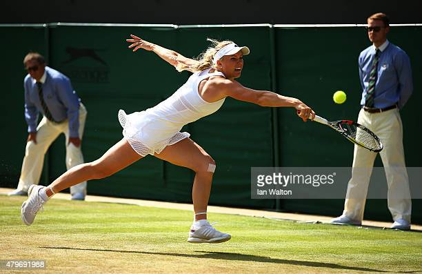 Caroline Wozniacki of Denmark plays a backhand in her Ladies' Singles Fourth Round match against Garbine Muguruza of Spain during day seven of the...