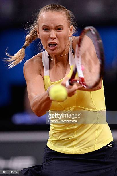 Caroline Wozniacki of Denmark plays a backhand in her match against Carla Suarez Navarro of Spain during Day 3 of the Porsche Tennis Grand Prix at...