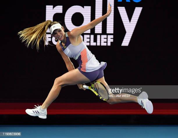 Caroline Wozniacki of Denmark plays a shot between her legs as she and other top players play in the Rally for Relief charity tennis match in support...