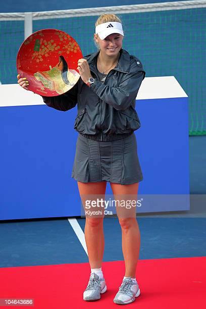 Caroline Wozniacki of Denmark poses with a trophy during the award ceremony after the Women's Singles final match against Elena Dementieva of Russia...