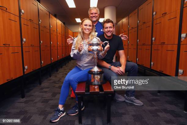 Caroline Wozniacki of Denmark poses with fiance David Lee and father Piotr with the Daphne Akhurst Trophy in the locker room after winning the...