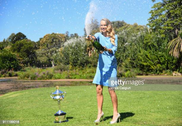 Caroline Wozniacki of Denmark poses with the Daphne Akhurst Memorial Cup and celebrates by spraying champagne in the Royal Botanical Gardens after...