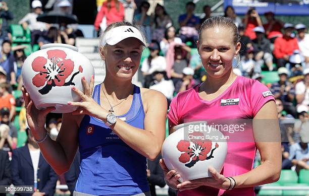 Caroline Wozniacki of Denmark poses with the KDB Korea Open championship trophy next to Kaia Kanepi of Estonia after her victory the final on day six...