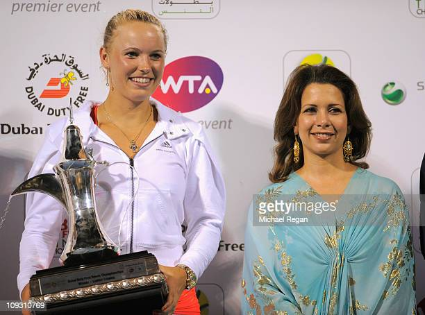 Caroline Wozniacki of Denmark poses with the trophy alongside Jordan's Princess Haya bint alHussein wife of Dubai ruler Sheikh Mohammed bin Rashed...