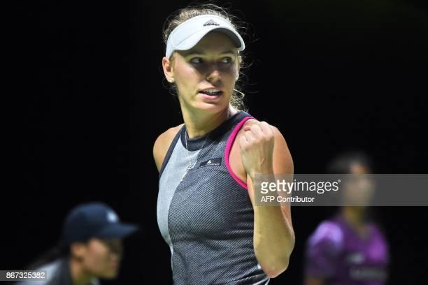 Caroline Wozniacki of Denmark reacts after a point against Karolina Pliskova of Czech Republic during the WTA Finals tennis tournament in Singapore...