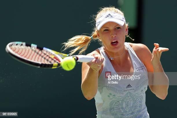 Caroline Wozniacki of Denmark returns a shot against Justine Henin of Belgium during day nine of the 2010 Sony Ericsson Open at Crandon Park Tennis...