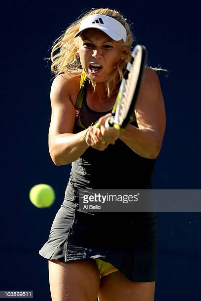 Caroline Wozniacki of Denmark returns a shot against Maria Sharapova of Russia during the women's singles match on day eight of the 2010 US Open at...