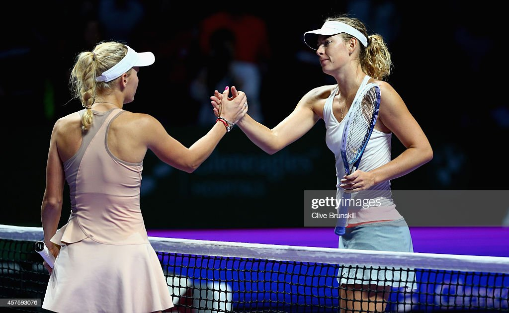 Caroline Wozniacki of Denmark shakes hands at the net after her three set victory against Maria Sharapova of Russia in their round robin match during the BNP Paribas WTA Finals at Singapore Sports Hub on October 21, 2014 in Singapore.
