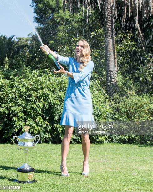 Caroline Wozniacki of Denmark sprays champagne with the Daphne Akhurst Memorial Cup after winning the 2018 Women's Singles Australian Open...