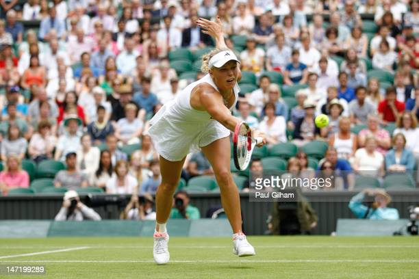 Caroline Wozniacki of Denmark stretches and hits a forehand return during her Ladies' singles first round match against Tamira Paszek of Austria on...