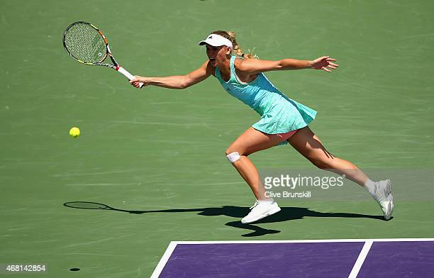 Caroline Wozniacki of Denmark stretches to play a forehand against Venus Williams of the United States in their fourth round match during the Miami...