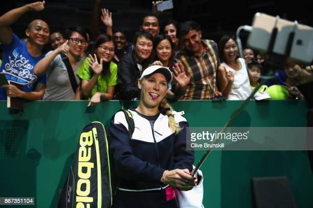 Caroline Wozniacki of Denmark takes a selfie with fans as she celebrates victory in her singles semi final match against Karolina Pliskova of Czech...