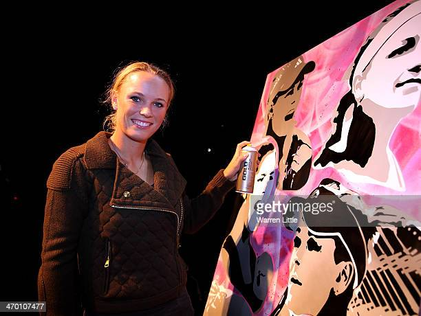 Caroline Wozniacki of Denmark trys her hand at stray painting during the players party during day two of the WTA Dubai Duty Free Tennis Championship...