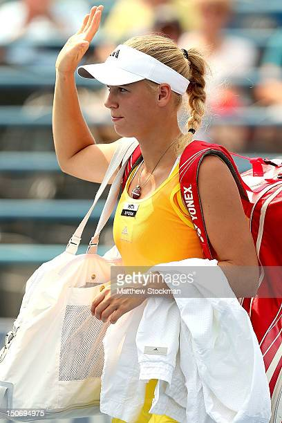 Caroline Wozniacki of Denmark waves to the crowd as she leaves the court after retiring from her match against Maria Kirilenko of Russia during the...