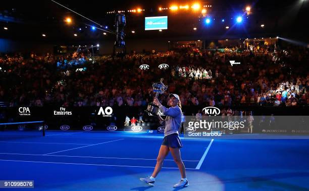 Caroline Wozniacki of Denmark waves to the crowd as she leaves the court with the Daphne Akhurst Trophy after winning the women's singles final...