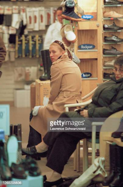 Carolyn Bessette seated in a shoe store in New York, perhaps Tik Tok shoes on W. 72nd street.