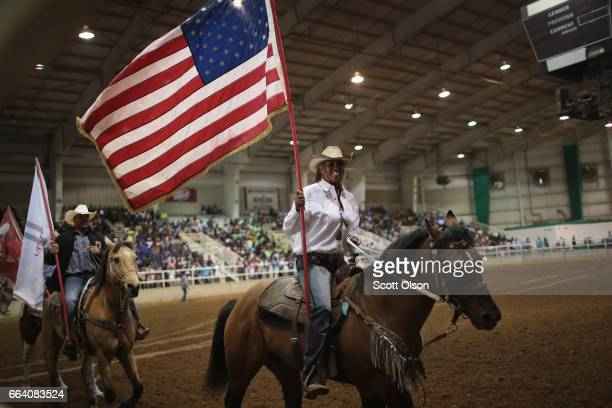 Carolyn Carter carries the American flag as contestants parade through the arena before the start of competition at the Bill Pickett Invitational...