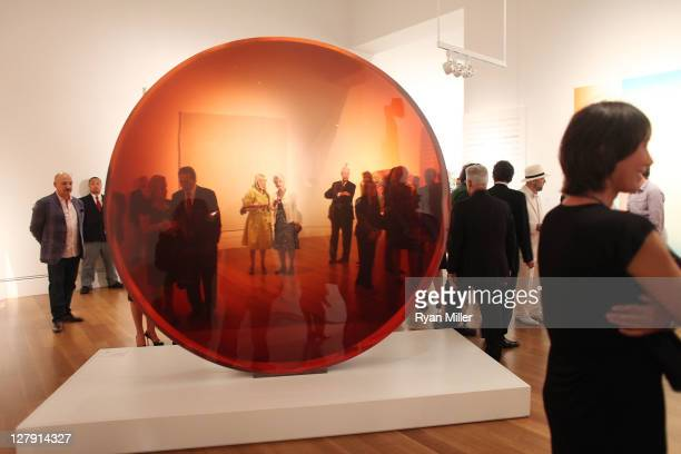 """Carolyn Graham and actress Angela Lansbury seen through De Wain Valentine's """"Red Concave Circle"""" during the Pacific Standard Time: Art in LA..."""