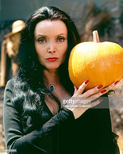 Carolyn Jones [1930-1983), US actress, in costume and holding a pumpkin in a publicity portrait issued for the US television series, 'The Addams...
