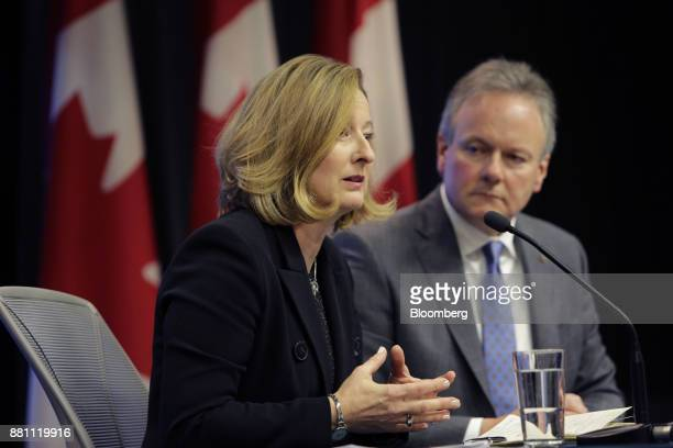 Carolyn Wilkins senior deputy governor at the Bank of Canada left speaks as Stephen Poloz governor of the Bank of Canada listens during a press...