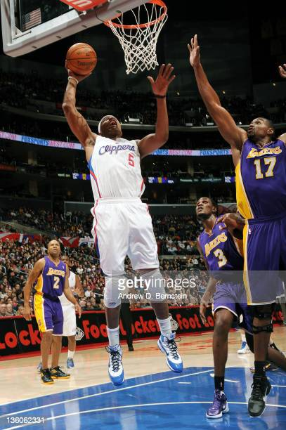 Caron Butler of the Los Angeles Clippers goes to the basket against Andrew Bynum and Devin Ebanks of the Los Angeles Lakers during the game at...