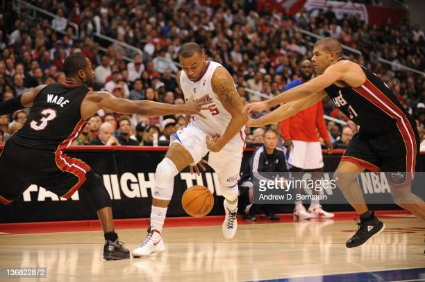 Caron Butler of the Los Angeles Clippers splits the defense of Dwyane Wade and Shane Battier of the Miami Heat at Staples Center on January 11 2012...