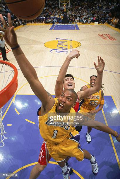 Caron Butler of the Los Angeles Lakers goes to the basket past Yao Ming of the Houston Rockets during a game at Staples Center on April 7 2005 in Los...