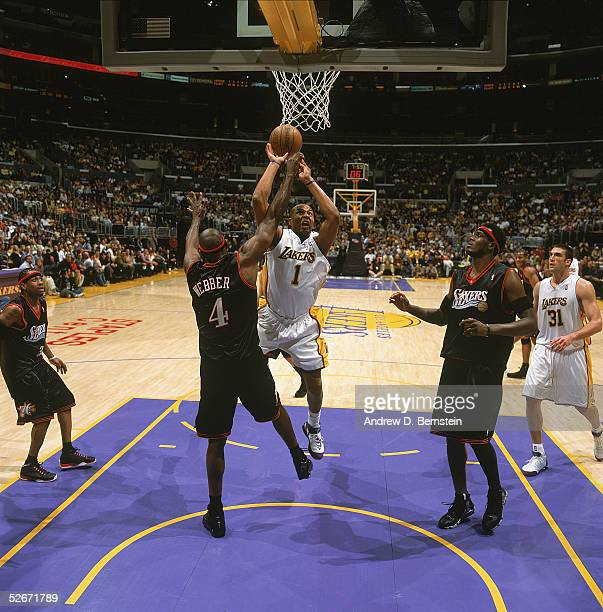 Caron Butler of the Los Angeles Lakers shoots against Chris Webber of the Philadelphia 76ers during the game at Staples Center on March 27 2005 in...