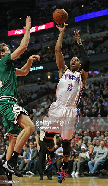 Caron Butler of the Oklahoma City Thunder shoots against Mike Dunleavy of the Chicago Bulls at the United Center on March 17 2014 in Chicago Illinois...
