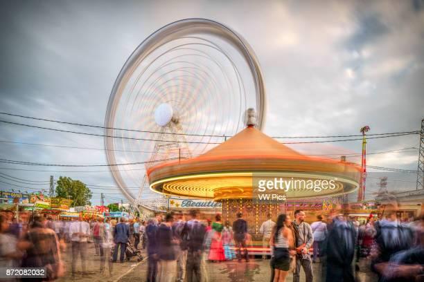 Carousel and Ferris wheel in a funfair Feria de Abril Seville Spain Long exposure shot