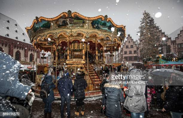 A carousel turns as snow falls at a Christmas market in Frankfurt western Germany on December 10 2017 / AFP PHOTO / dpa / Frank Rumpenhorst / Germany...