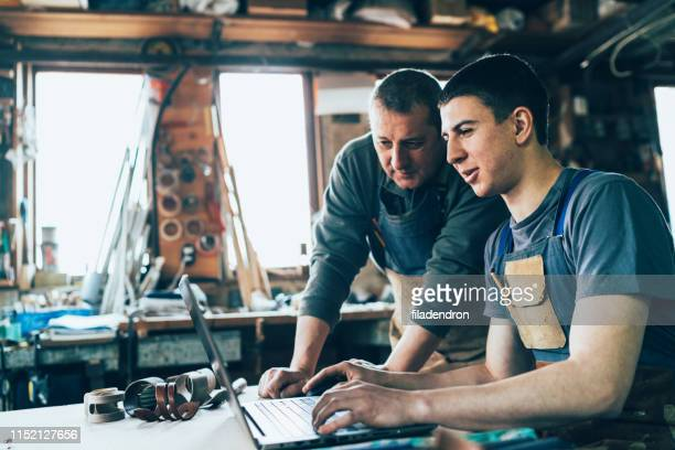 carpenter and his assistant working on laptop - two generation family stock pictures, royalty-free photos & images