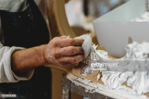 carpenter applying a silver lining on a frame - filippo sugar stock pictures, royalty-free photos & images