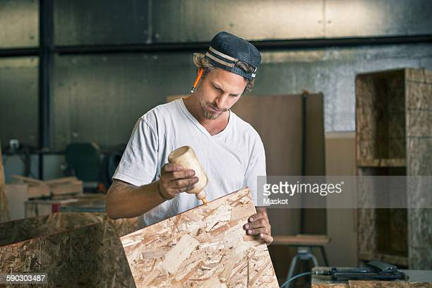 carpenter applying glue on wooden plank at workshop - collant photos et images de collection