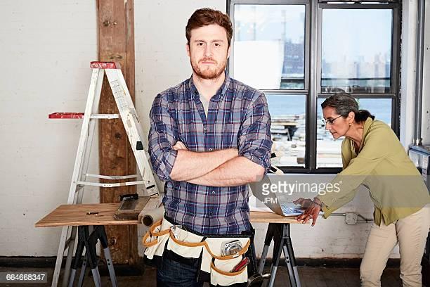Carpenter, arms crossed looking at camera