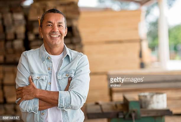 Carpenter at his carpentry looking happy