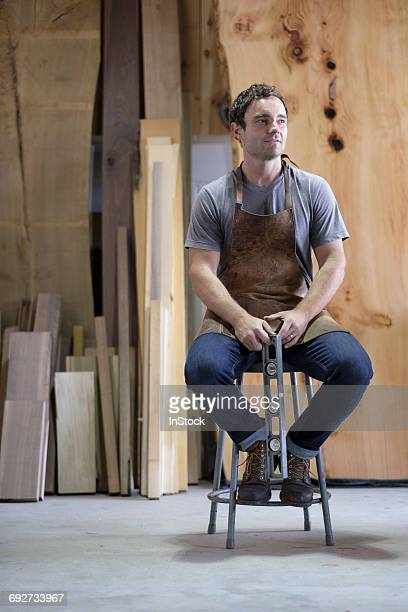 carpenter at his workshop, holding woodwork tool - artisan photos et images de collection