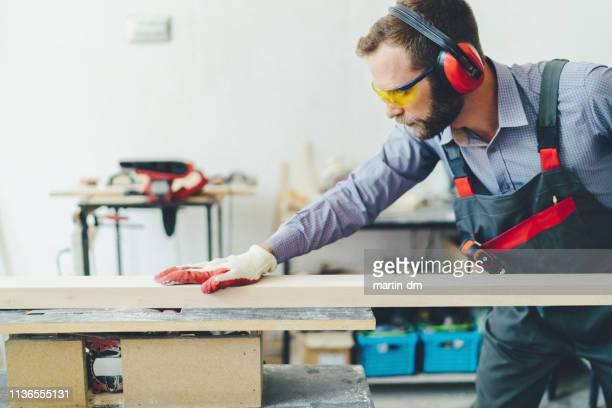 carpinteiro na oficina que processa pranchas - cortando atividade - fotografias e filmes do acervo