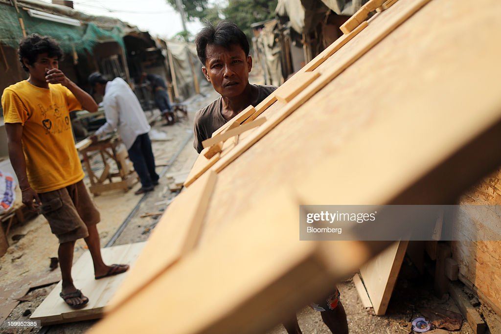 A carpenter carries lumber at a workshop in Bangkok, Thailand, on Wednesday, Jan. 23, 2013. Prime Minister Yingluck Shinawatra's government last month approved a new round of increases in the daily minimum wage to 300 baht ($9.8) from the beginning of this year, after a similar raise in April in seven provinces including Bangkok. Photographer: Dario Pignatelli/Bloomberg via Getty Images