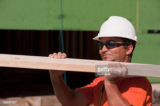 Carpenter carrying a wooden rafter