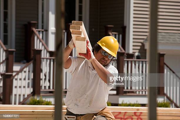 Carpenter carrying planks at a construction site