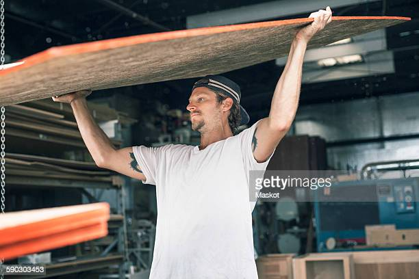 carpenter carrying wooden plank at workshop - vanguardians stock pictures, royalty-free photos & images
