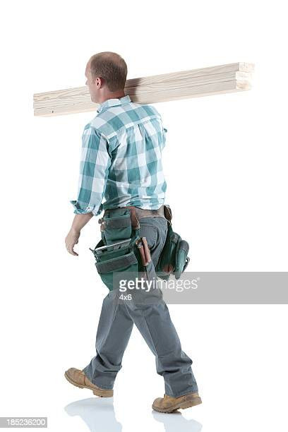 Carpenter carrying wooden planks on his shoulders
