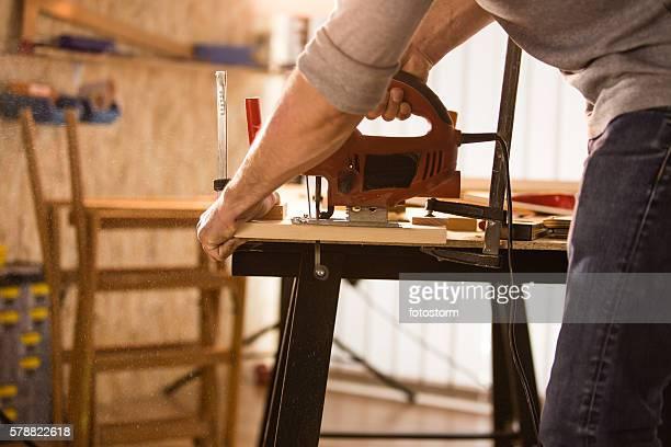 Carpenter cutting a wood using jigsaw cutter