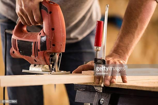 carpenter cutting a wood using jigsaw cutter - 電動糸のこ ストックフォトと画像