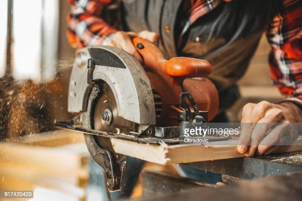 carpenter cutting plank by circular saw - circular saw stock photos and pictures