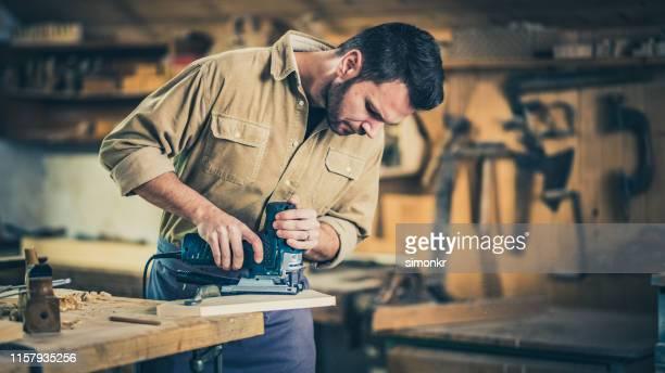 ワークショップで木材を切断する大工 - 電動糸のこ ストックフォトと画像