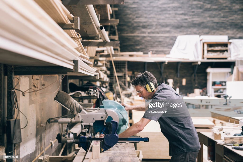 Carpenter cutting wood : Stock Photo